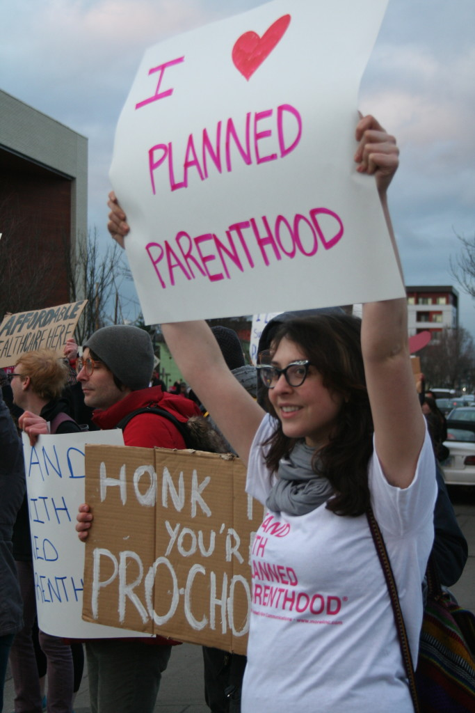 "A woman holds an ""I heart Planned Parenthood"" sign."
